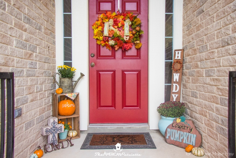 This colorful fall front porch stands out with a bright red front door and pops of orange pumpkins